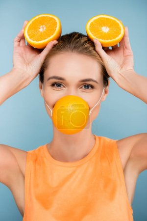 young woman in citrus protective mask holding orange halves on blue