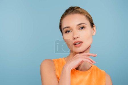 sinnliche Frau mit natürlichem Make-up, die isoliert auf blauem Grund in die Kamera blickt