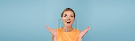 excited woman in orange singlet looking up isolated on blue, banner