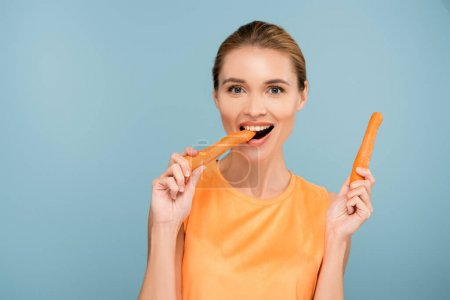 Photo for Pleased woman looking at camera while eating whole carrot isolated on blue - Royalty Free Image