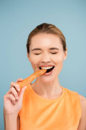 cheerful young woman with natural makeup biting whole carrot isolated on blue