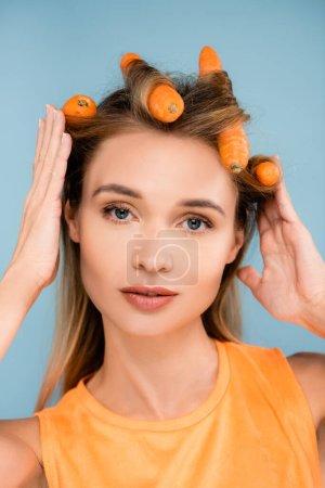 hübsche Frau mit natürlichem Make-up mit Karotten als Lockenwickler isoliert auf blau