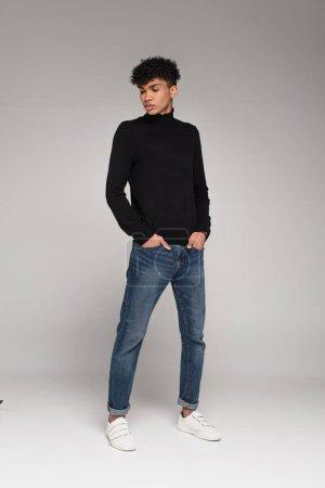 Photo pour Pleine longueur d'homme afro-américain percé en jeans debout avec les mains dans les poches sur gris - image libre de droit