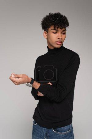 Photo pour Jeune homme afro-américain ajustant sa manche sur pull col roulé isolé sur gris - image libre de droit