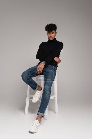 in voller Länge junger afrikanisch-amerikanischer Mann in Rollkragenpullover und Jeans sitzt auf Stuhl, während er auf grau posiert