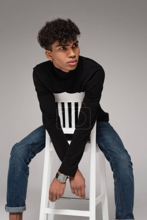 Photo for Curly african american model in turtleneck sweater sitting on chair while posing isolated on grey - Royalty Free Image