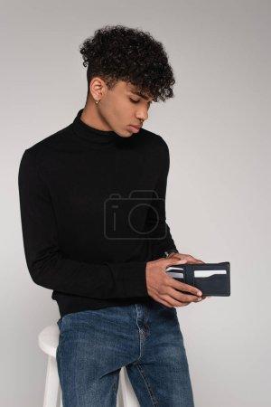 Photo pour Jeune homme afro-américain regardant à l'intérieur du portefeuille en cuir isolé sur gris - image libre de droit