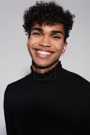 curly african american man in black turtleneck sweater smiling isolated on grey