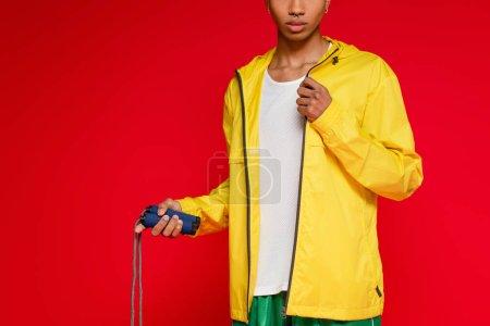 Photo pour Vue recadrée de l'homme afro-américain sportif veste de pluie jaune tenant corde sautante isolé sur rouge - image libre de droit