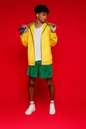 Photo for Full length of sportive african american man in yellow rain jacket standing with skipping rope on red - Royalty Free Image