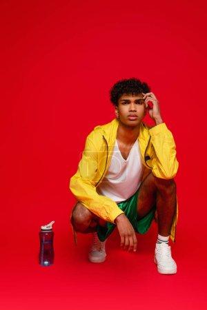 Photo pour Bouclé homme afro-américain en veste de pluie jaune assis près de la bouteille de sport sur rouge - image libre de droit