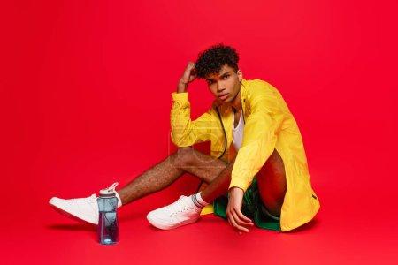 Photo pour Jeune homme afro-américain en veste de pluie jaune assis près d'une bouteille de sport sur rouge - image libre de droit
