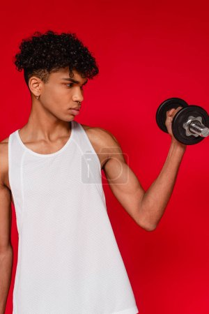 muscular african american man in tank top working out with dumbbell isolated on red