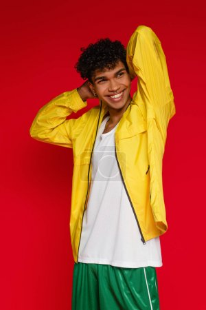 cheerful african american man in jacket and shorts posing on red