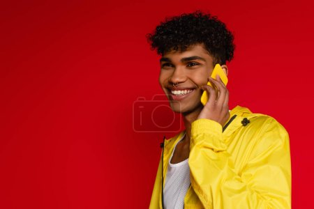 happy african american man in jacket talking on smartphone on red