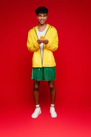 Photo pour Pleine longueur de heureux homme afro-américain en veste tenant smartphone sur rouge - image libre de droit