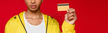 partial view of african american man in jacket holding credit card isolated on red, banner