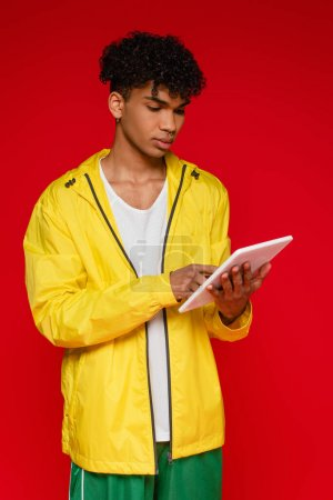 curly african american man in jacket using digital tablet isolated on red