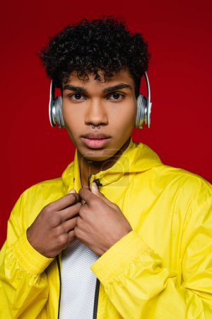 african american man in yellow jacket listening music in wireless headphones isolated on red