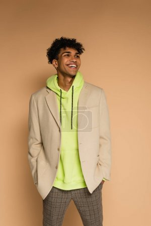 trendy african american man in hoodie and blazer smiling on beige