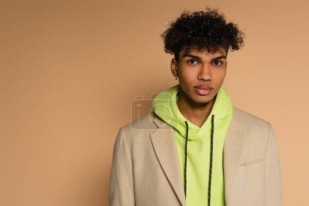 trendy african american man in hoodie and blazer looking at camera on beige