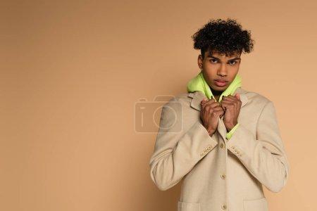 joven afroamericano hombre ajustando blazer en beige