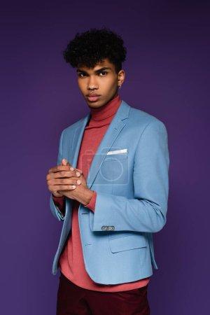 Photo pour Jeune homme afro-américain dans blazer élégant regardant la caméra sur violet - image libre de droit