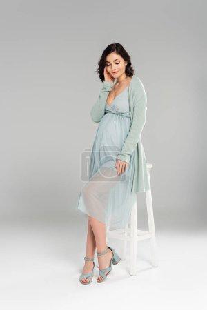 Photo pour Jolie femme enceinte posant près de chaise blanche sur fond gris - image libre de droit