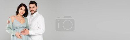 Photo pour Jeune homme embrassant jolie femme enceinte isolé sur gris, bannière - image libre de droit