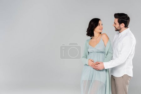 Pregnant woman smiling at husband isolated on grey