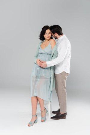 Photo pour Homme étreignant femme enceinte près de chaise blanche sur fond gris - image libre de droit