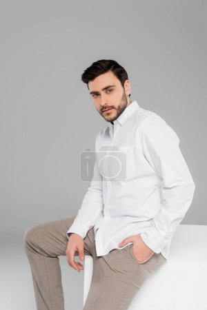 Stylish man holding hand in pocket of pants and looking at camera on cube on grey background