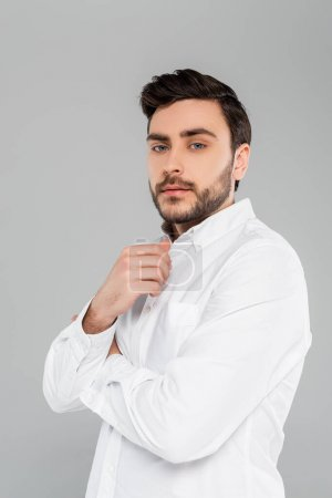 Brunette man in white shirt looking at camera isolated on grey