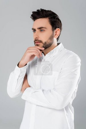 Photo for Young man in white shirt holding hand near chin isolated on grey - Royalty Free Image