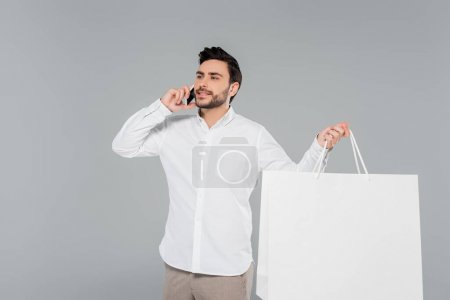 Smiling man holding shopping bag and talking on mobile phone isolated on grey