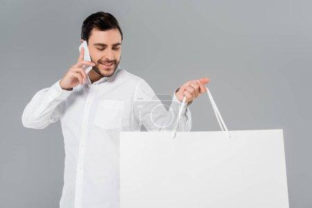 Photo pour Homme joyeux en chemise blanche tenant sac à provisions et parlant sur téléphone portable isolé sur gris - image libre de droit