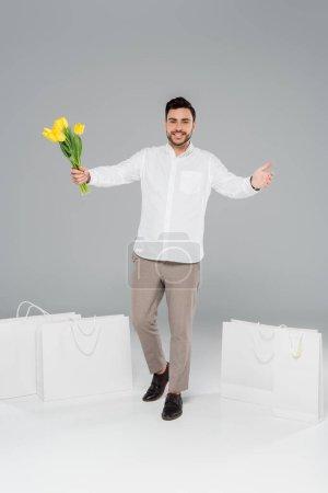 Photo pour Homme joyeux tenant des tulipes près des sacs à provisions sur fond gris - image libre de droit