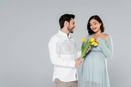 Smiling man giving flowers to pregnant wife isolated on grey