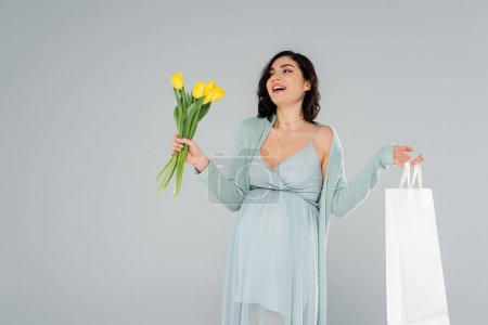 Photo pour Joyeux femme enceinte en robe tenant sac à provisions et fleurs isolées sur gris - image libre de droit