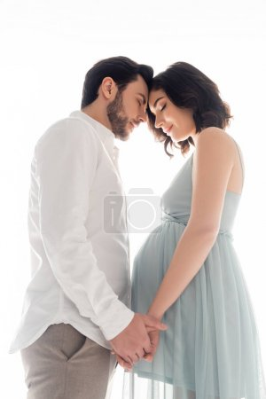 Photo for Low angle view of pregnant woman with closed eyes holding hands of husband isolated on white - Royalty Free Image