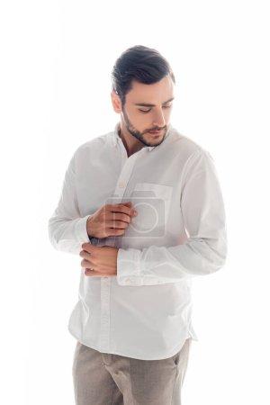 Photo pour Jeune homme manche de fixation de chemise blanche isolé sur blanc - image libre de droit