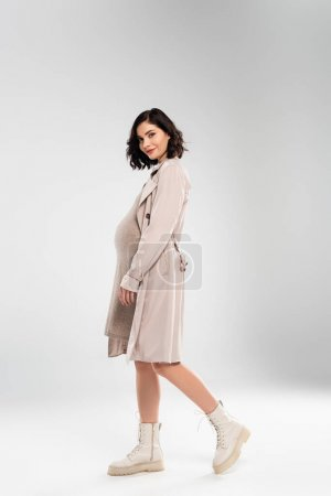 Trendy pregnant woman walking on grey background