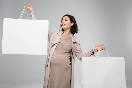 Photo pour Joyeux femme enceinte tenant des sacs à provisions sur fond gris - image libre de droit