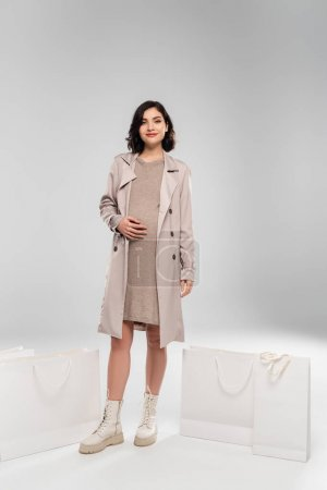 Smiling pregnant woman in coat standing near shopping bags on grey background