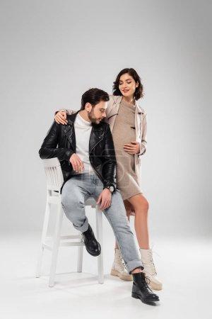 Photo pour Femme enceinte élégante étreignant mari sur chaise sur fond gris - image libre de droit