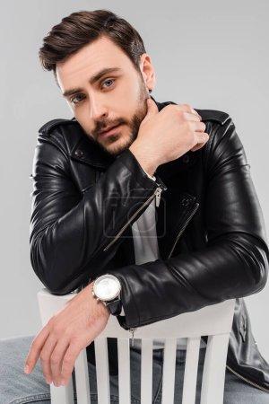 Mann in schwarzer Lederjacke blickt in Kamera auf Stuhl isoliert auf grau