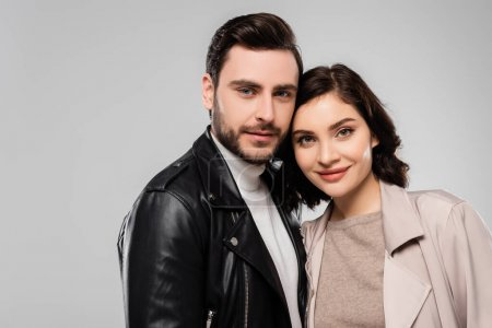 Young stylish couple looking at camera isolated on grey