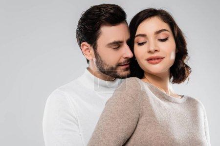 Junger Mann mit geschlossenen Augen steht neben Frau isoliert auf grau