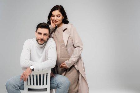 Photo pour Femme enceinte en robe et manteau debout près du mari sur chaise isolée sur gris - image libre de droit