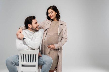 Photo pour Gaie femme enceinte regardant mari sur chaise isolé sur gris - image libre de droit